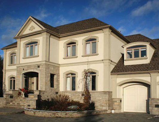 Classic Exterior Design of Custom Home with Stucco and Stone Siding by Exterior by Design Oakville